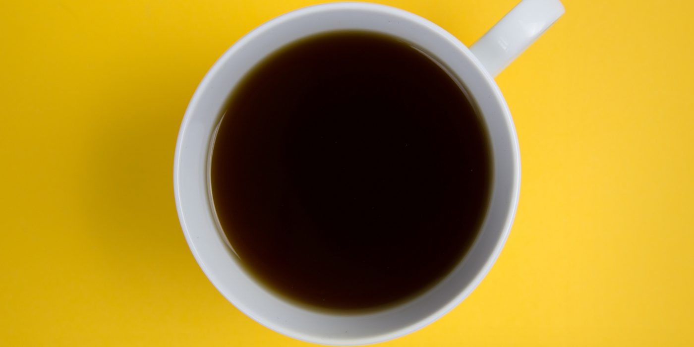 Cup of coffee on yellow background